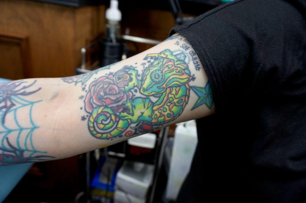 腕のカメレオンのタトゥー