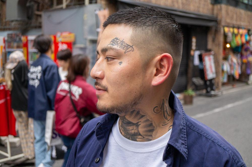 レタリングタトゥー・顔にワンポイントタトゥーの男性